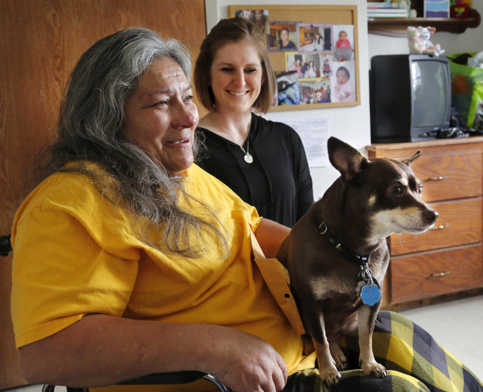 Photo - Ida Hernandez, left, a homeless woman, was badly injured in the May 19, 2013, tornado that hit Shawnee and Bethel Acres. She was separated from her dog, Bella, when they were riding in a truck that was blown off Interstate 40. Callie McKee, right, a physical therapist from OU Health Sciences Center got involved, located Ida's pet and eventually reunited the woman and her dog. Now, the therapist brings Bella to a nursing home/rehab facility in Midwest City where Ida stays.  Photo by Jim Beckel, The Oklahoman  Jim Beckel -  THE OKLAHOMAN