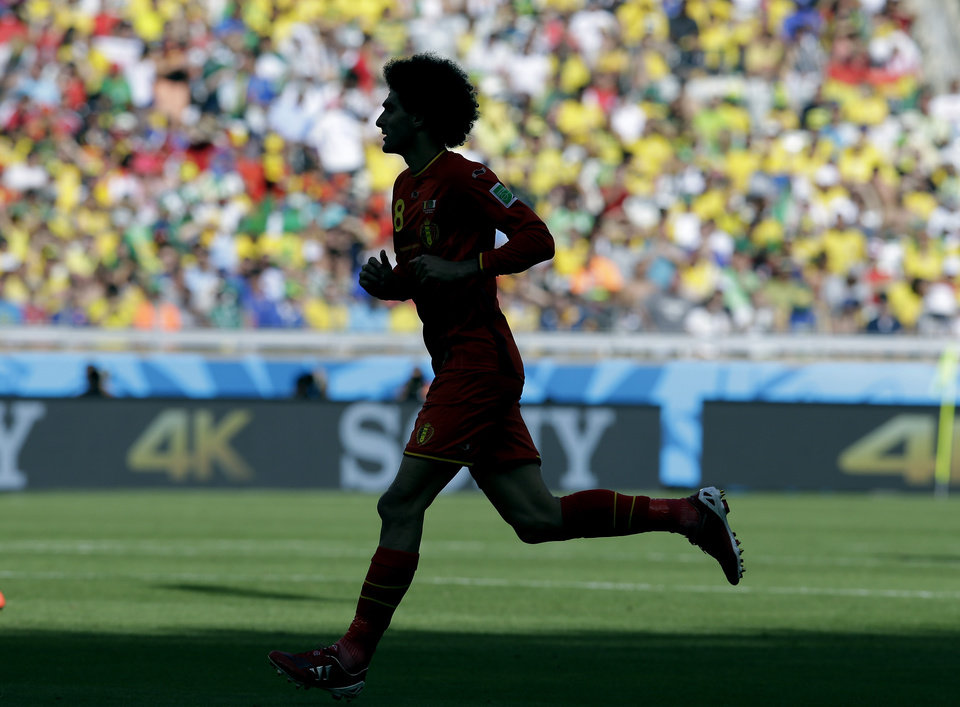 Photo - Belgium's Marouane Fellaini runs onto the pitch after coming on as a substitute during the group H World Cup soccer match between Belgium and Algeria at the Mineirao Stadium in Belo Horizonte, Brazil, Tuesday, June 17, 2014. (AP Photo/Hassan Ammar)