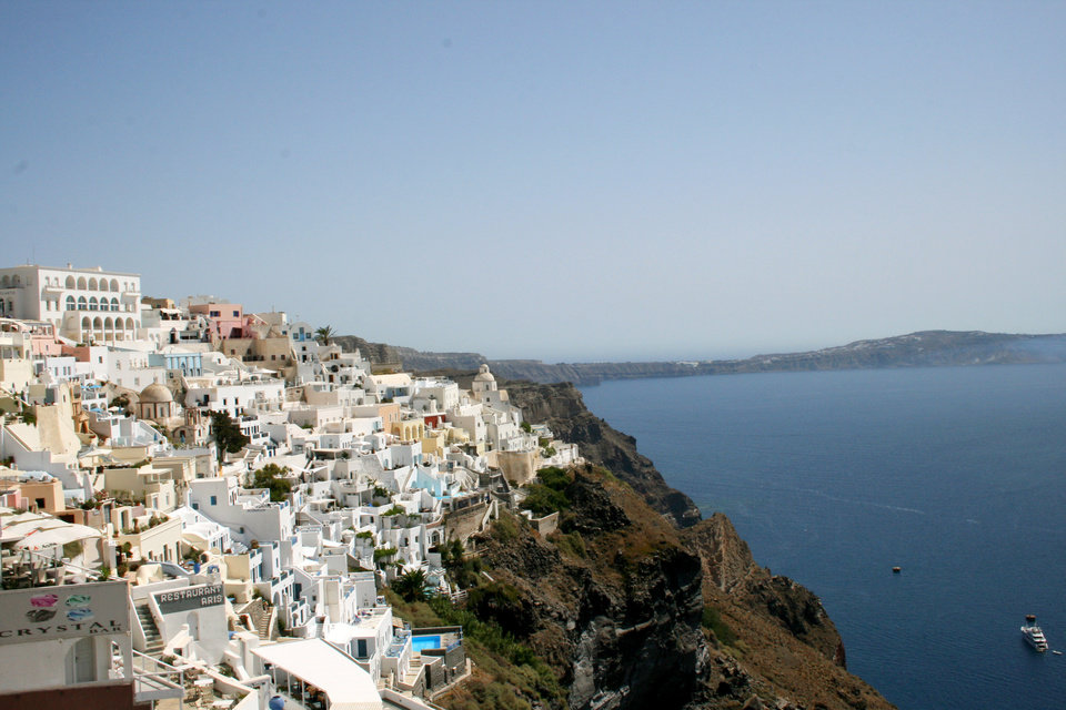 Photo - This July 2014 photo shows whitewashed homes stacked like sugar cubes on the seaside cliffs of Santorini, part of Greece's Cyclades island chain in the Aegean Sea. The Cyclades are known for panoramic waterfront views, black-sand beaches and dramatic sunsets. (AP Photo/Kristi Eaton)