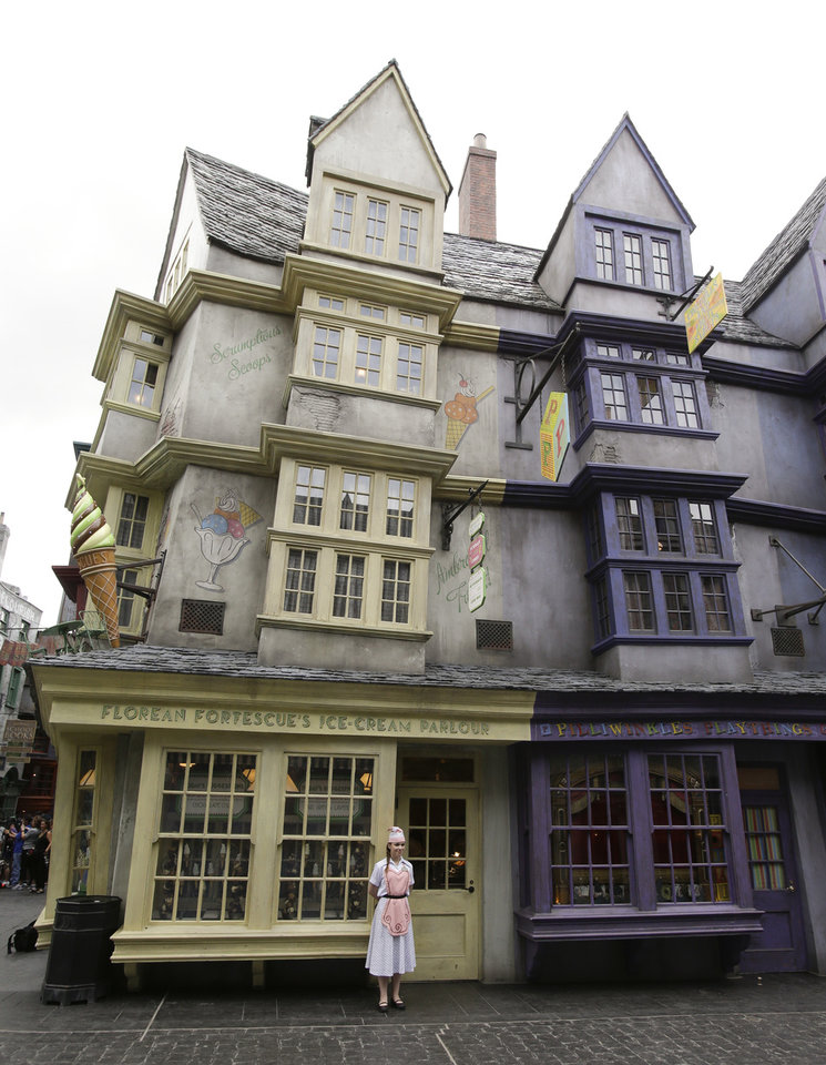 Photo - A girl stands in front of Florian Fortescue's Ice Cream Parlour during a preview of Diagon Alley at the Wizarding World of Harry Potter at Universal Orlando, Thursday, June 19, 2014, in Orlando, Fla. (AP Photo/John Raoux)