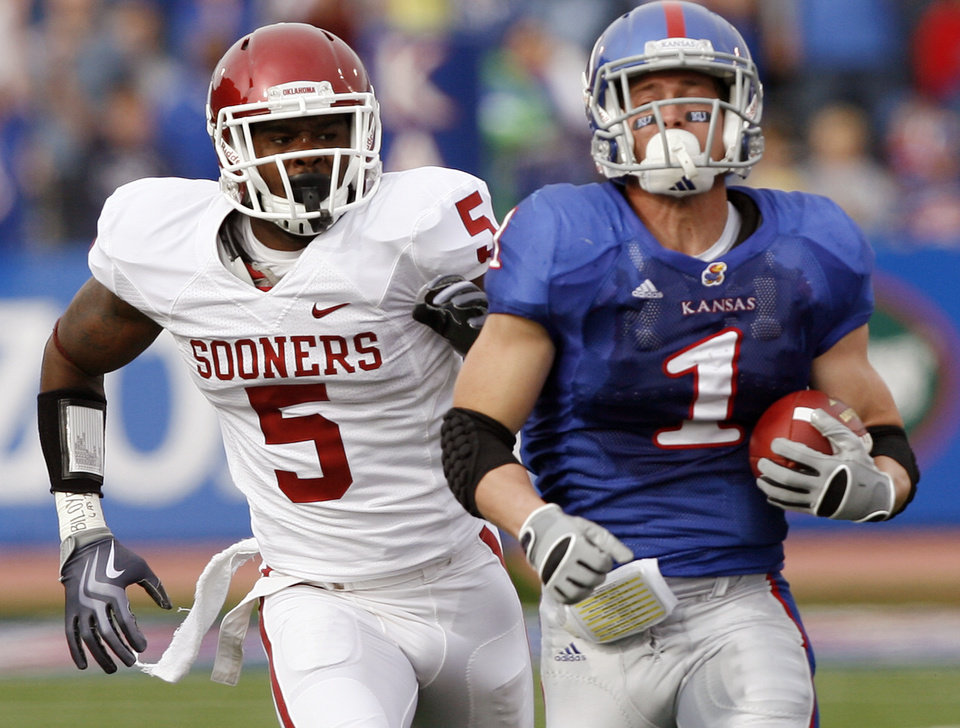 Photo - Oklahoma's Joseph Ibiloye (5) chases down Kansas' Jake Sharp (1) during the first half of the college football game between the University of Oklahoma Sooners (OU) and the University of Kansas Jayhawks (KU) on Saturday, Oct. 24, 2009, in Lawrence, Kan. Photo by Chris Landsberger, The Oklahoman