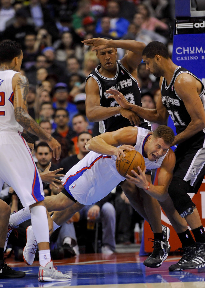 Photo - Los Angeles Clippers forward Blake Griffin, bottom middle, dives for the loose ball as San Antonio Spurs forward Boris Diaw (33), of France, and forward Tim Duncan (21) look on in the first half of a NBA basketball game, Tuesday, Feb. 18, 2014, in Los Angeles.(AP Photo/Gus Ruelas)