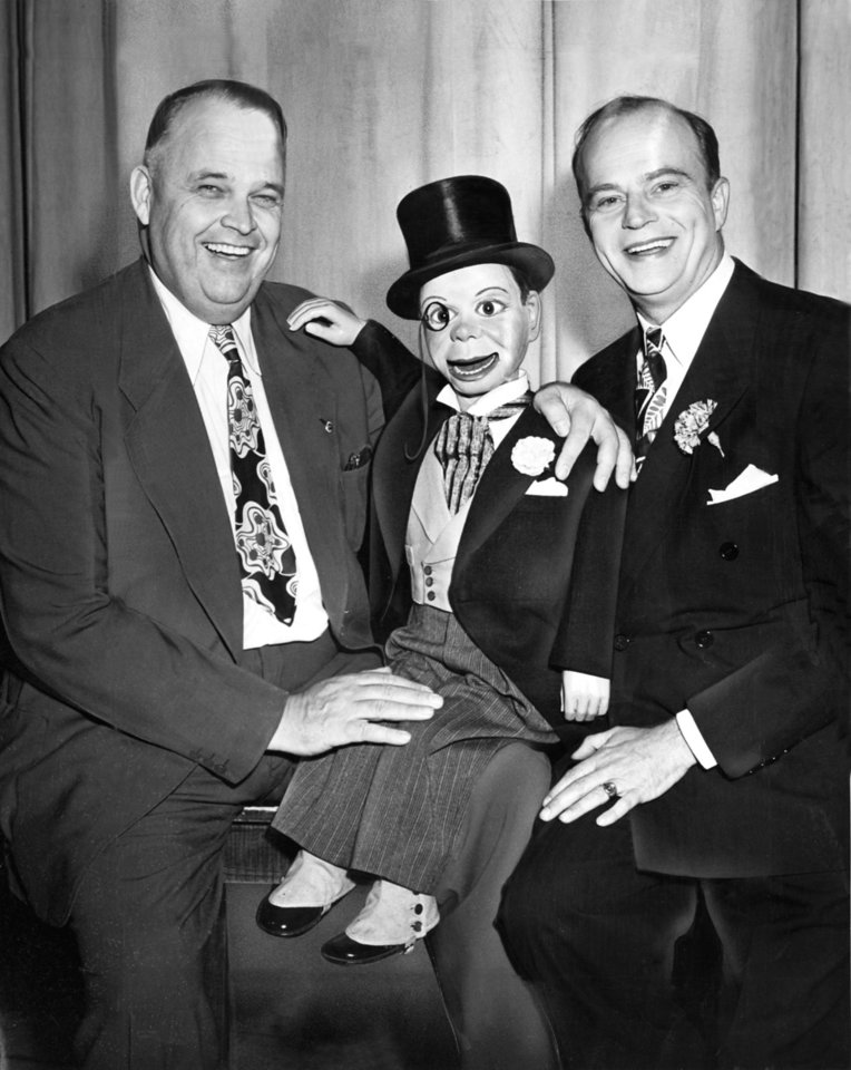 "ROBERT S. KERR / EDGAR BERGEN / CHARLIE McCARTHY:  ""You know, Charlie,"" mused the governor Monday night as he surveyed the seam-busting crowd at the auditorium, ""I never knew of but one other little man who could draw a mob like this.""  Charlie naturally, was curious.  ""The other little man,"" grinned the governor, ""was Dewey.""  Cynical Republicans wondered how the governor knew, because he wasn't even in town when Dewey packed the auditorium for a campaign speech last summer.  Anyhow, that sort of badinage went on as Governor (Robert S.) Kerr, Charlie McCarthy and Edgar Bergen mugged shamelessly for the cameraman. Staff photo by Bill Stockwell taken 5/21/45; photo ran in the 5/22/45 Daily Oklahoman."