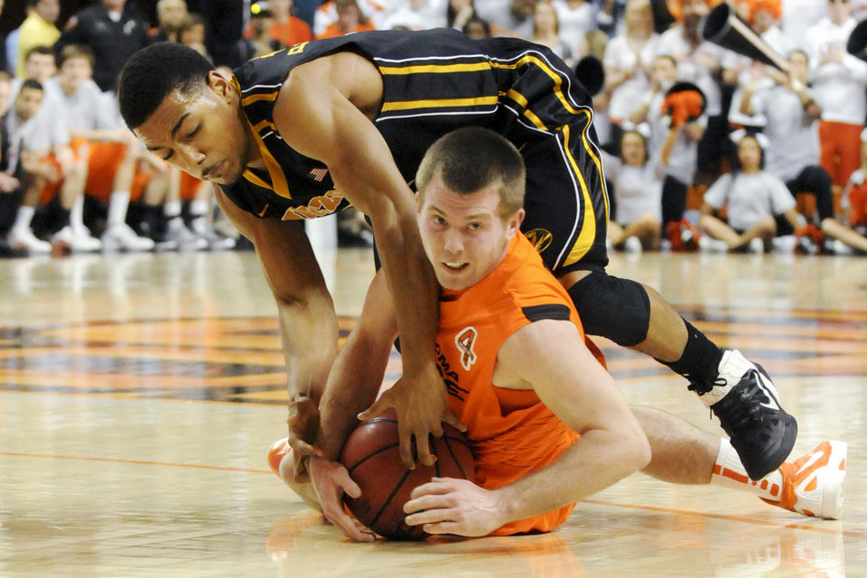 Oklahoma State guard Keiton Page, bottom, and Missouri guard Phil Pressey, top, struggle for a loose ball during the first half of an NCAA college basketball game in Stillwater, Okla., Wednesday, Jan. 25, 2012. (AP Photo/Brody Schmidt) ORG XMIT: OKBS102