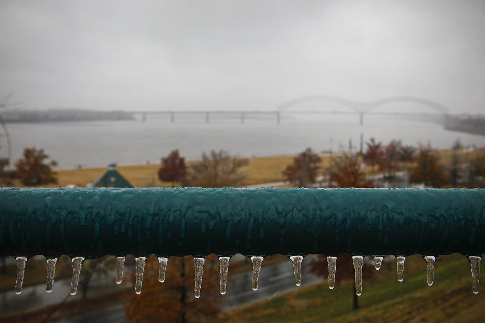 Photo - Icicles begin to form on the railings of the river walk as freezing rain falls Friday, Dec. 6, 2013, in Memphis, Tenn.  National Weather Service said winter storm warnings and watches and an ice storm warning were in effect for northern Mississippi and West Tennessee on Friday. (AP Photo/The Commercial Appeal, William DeShazer)