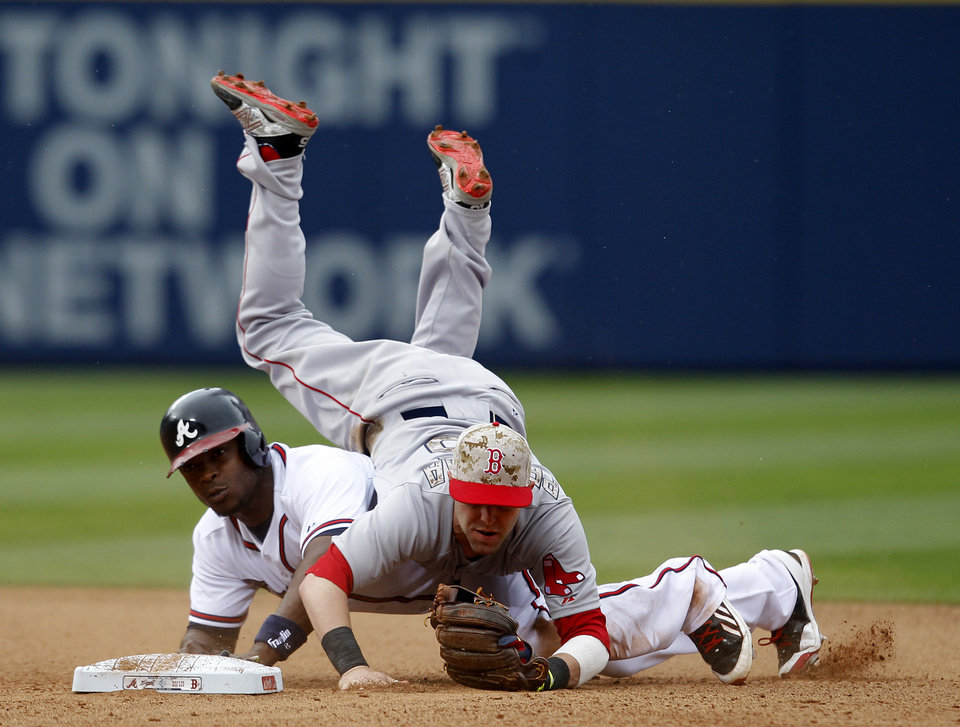 Photo - Boston Red Sox's Dustin Pedroia (15) flips over Atlanta Braves' Justin Upton after throws to first base for the double play during the sixth inning of a baseball game on Monday, May 26, 2014, in Atlanta, Ga. (AP Photo/Butch Dill)