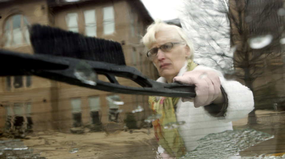 Nancy Mergler, University of Oklahoma  Provost, clears her windshield to head home at 1:15 pm.   President David Boren called off classes for the remainder of Thursday and all of Friday as a winter storm moved into the area on Thursday,  Jan. 28, 2010, in Norman, Okla.  Photo by Steve Sisney, The Oklahoman
