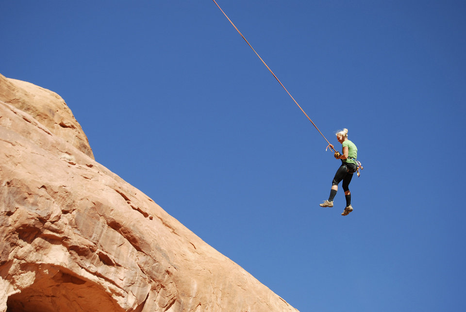Photo - In this Nov. 4, 2012 photo, a person swings on the Corona Arch near Moab, Utah. The arch has become popular for daredevil rope-swinging after climbers figured out how to adapt climbing gear to set up a pendulum ride under the arch. Federal officials are considering outlawing the stunt made so popular on YouTube that state authorities banned from commercial outfitters in 2013. (AP Photo/The Salt Lake Tribune, Brian Maffly)  DESERET NEWS OUT; LOCAL TELEVISION OUT; MAGS OUT