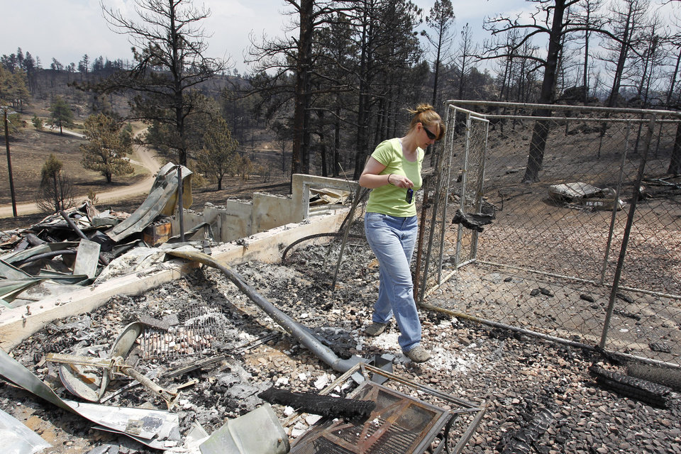Photo - Teresa Jiles walks through the remains of her home that was destroyed by the High Park Fire in the Glacier View residential area near Livermore, Colo., on Monday, July 2, 2012. The last evacuees from the fire in have been allowed to return home as crews fully contained the136-square-mile wildfire that killed one resident and destroyed 259 houses. (AP Photo/Ed Andrieski) ORG XMIT: COEA102