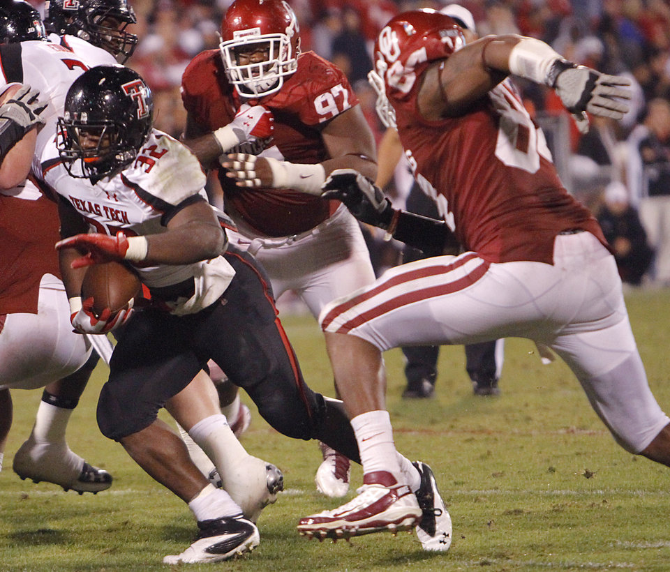 Photo - Texas Tech's Aaron Crawford (32) runs past Oklahoma's Jamarkus McFarland (97) and Frank Alexander (84) during the college football game between the University of Oklahoma Sooners (OU) and Texas Tech University Red Raiders (TTU) at the Gaylord Family-Oklahoma Memorial Stadium on Sunday, Oct. 23, 2011. in Norman, Okla. Photo by Chris Landsberger, The Oklahoman