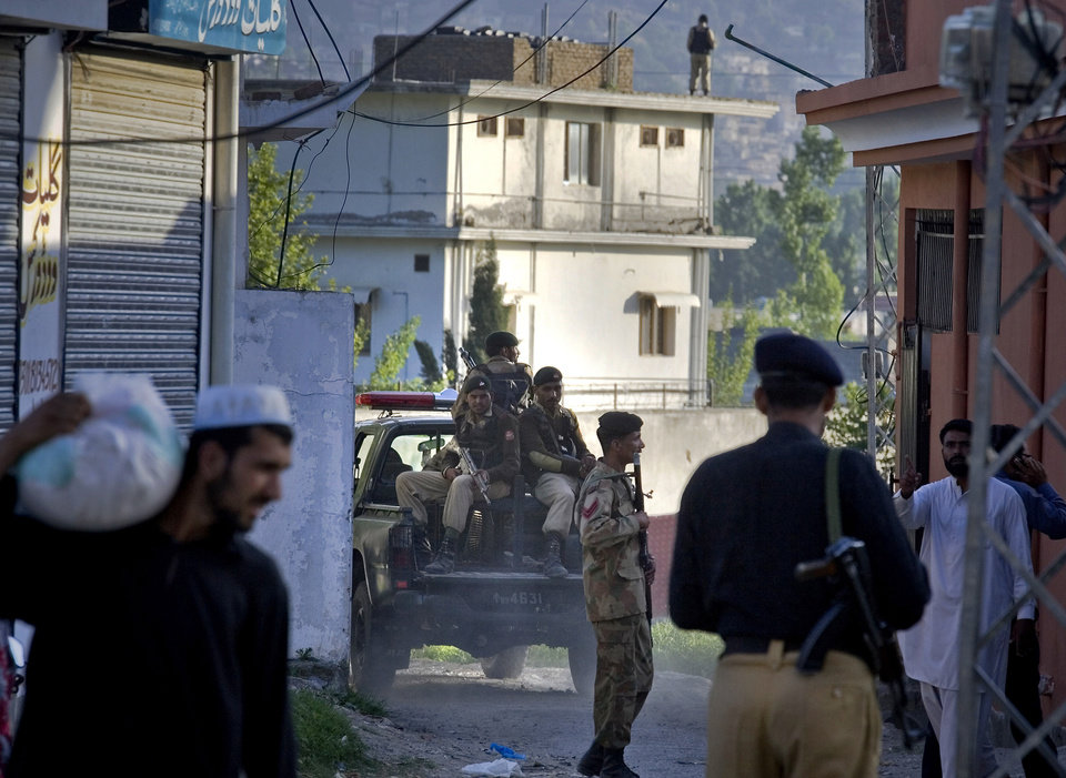 Photo - Pakistan army soldiers and police officers patrol past house, background, where it is believed al-Qaida leader Osama bin Laden lived in Abbottabad, Pakistan on Monday, May 2, 2011. Bin Laden, the mastermind behind the Sept. 11, 2001, terror attacks that killed thousands of people, was slain in his hideout in Pakistan early Monday in a firefight with U.S. forces, ending a manhunt that spanned a frustrating decade. (AP Photo/Anjum Naveed)