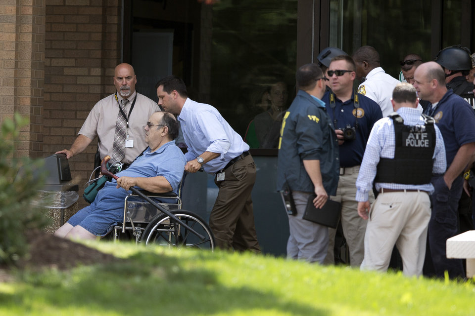 Photo - A patient is evacuated from the scene of a shooting at the Mercy Fitzgerald Hospital in Darby, Pa. on Thursday, July 24, 2014. A prosecutor said a gunman opened fire inside the psychiatric unit leaving one hospital employee dead and a second injured before being critically wounded himself. (AP Photo)