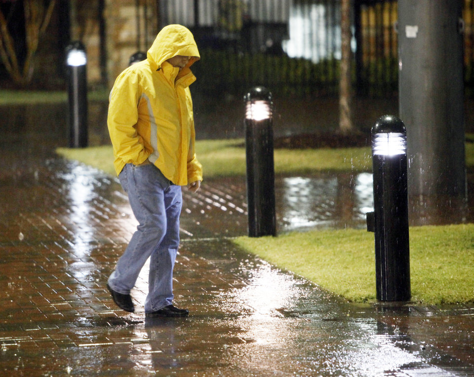 Photo - A man walks through the rain during a weather delay before a college football game between the Oklahoma State University Cowboys and the University of Tulsa Golden Hurricane at H.A. Chapman Stadium in Tulsa, Okla., Saturday, Sept. 17, 2011. Photo by Nate Billings, The Oklahoman