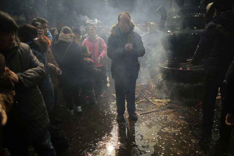 Photo - A man burns joss sticks while praying at Longhua Temple on the first day of the Lunar New Year in Shanghai, China on Sunday, Feb. 10, 2013.  Millions across China are celebrating the arrival of the Lunar New Year, the Year of the Snake, marked with a week-long Spring Festival holiday.   (AP Photo/Eugene Hoshiko)
