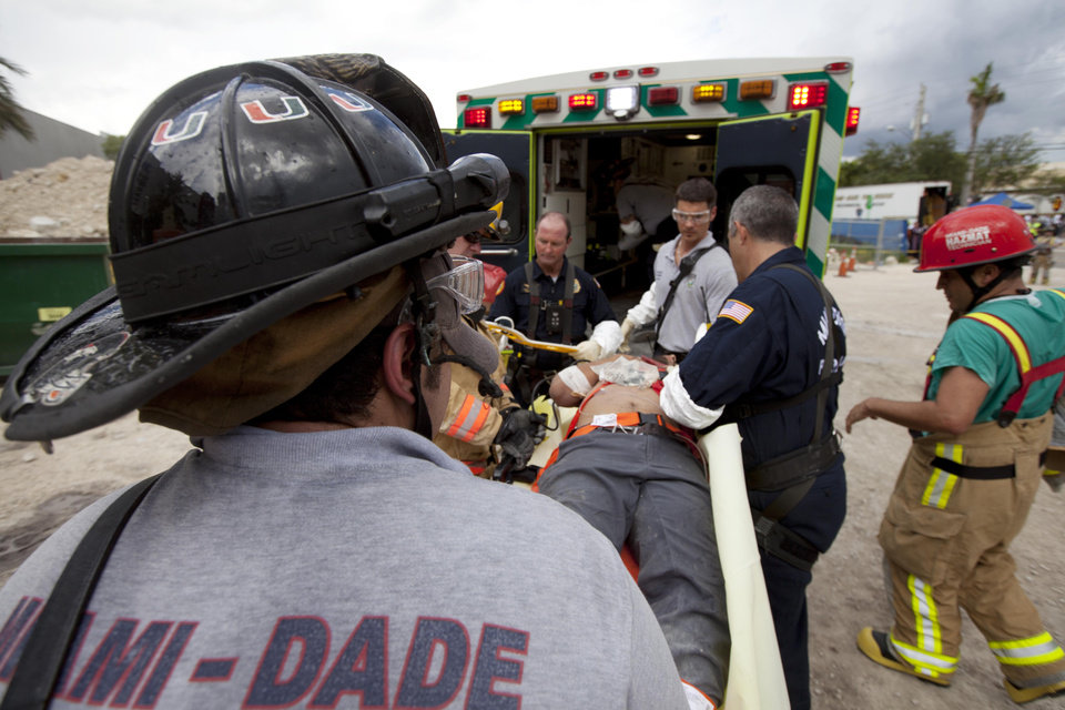 In this photo provided by Miami-Dade Fire Rescue, emergency workers bring an injured man to an ambulance after a section of a parking garage under construction at a Miami-Dade College campus collapsed, Wednesday, Oct. 10, 2012 in Doral, Fla., killing one worker and trapping at least two others in the rubble, officials said. (AP Photo/Miami-Dade Fire Rescue)