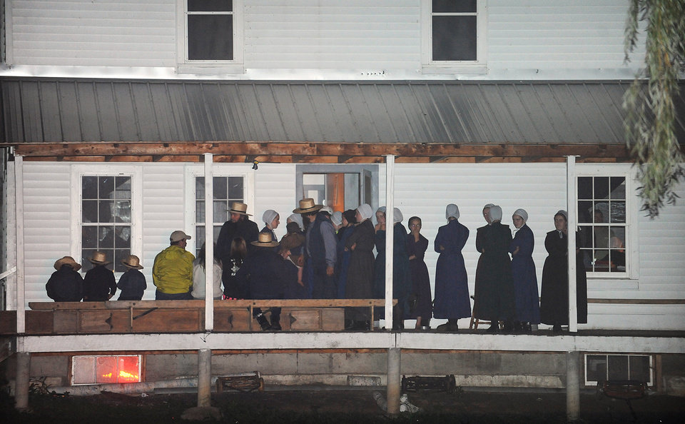 Photo - Supporters gather on the porch of a house at the intersection of Route 812 and Mt. Alone Road in Heuvelton, NY on Thursday, Aug. 14, 2014 after Fannie Miller, 12, and her sister Delila Miller, 6, were returned home safely after being abducted Wednesday night at a farm stand near their home. (AP Photo/The Watertown Daily Times, Jason Hunter)