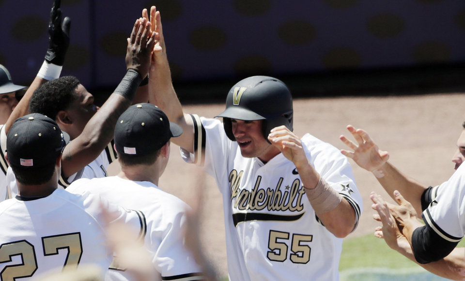 Vanderbilt's Conrad Gregor (55) is congratulated by teammates after scoring on a throwing error by South Carolina pitcher Jordan Montgomery in the second inning of a Southeastern Conference tournament college baseball game at the Hoover Met in Hoover, Ala., Thursday, May 23, 2013. (AP Photo/Dave Martin)