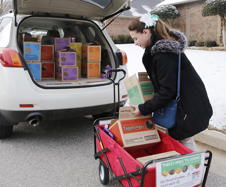 Girl Scout Katie Francis moves boxes back into the car after selling cookies in a neighborhood Wednesday, February 5, 2014. Photo by Doug Hoke, The Oklahoman