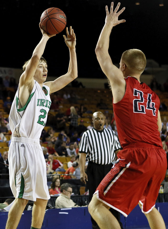 Photo - Brian Canfield (21) of Bishop McGuinness looks to pass around Matt Craig (24) of Bishop Kelley during a Class 5A boys semifinal game in the state basketball championship tournament between Bishop McGuinness and Bishop Kelley at the Mabee Center in Tulsa, Okla., Friday, March 14, 2014. Photo by Nate Billings, The Oklahoman