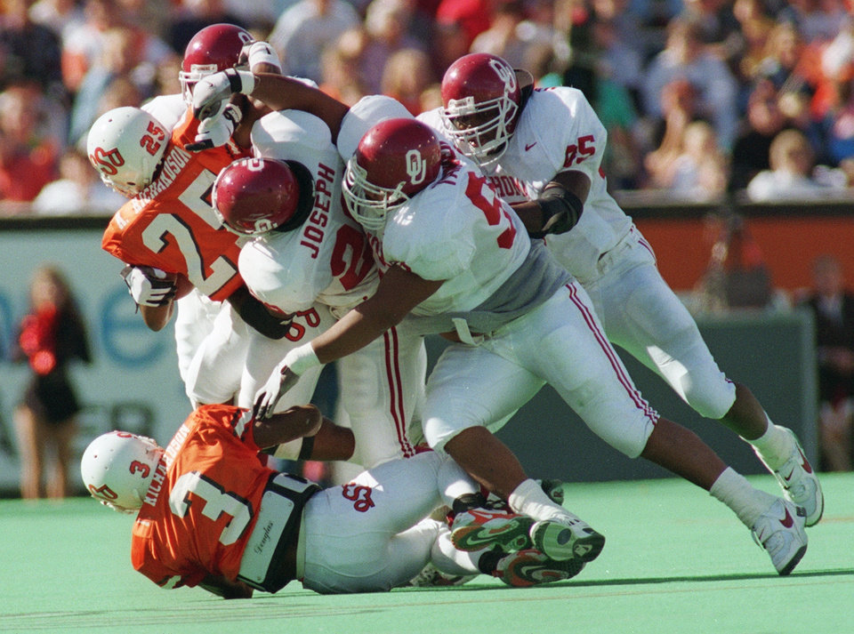 Photo - OU defenders swallow OSU's Andre Richardson during the Bedlam college football game on Nov. 9, 1996 in Stillwater, Okla. Photo by Doug Hoke, The Oklahoman