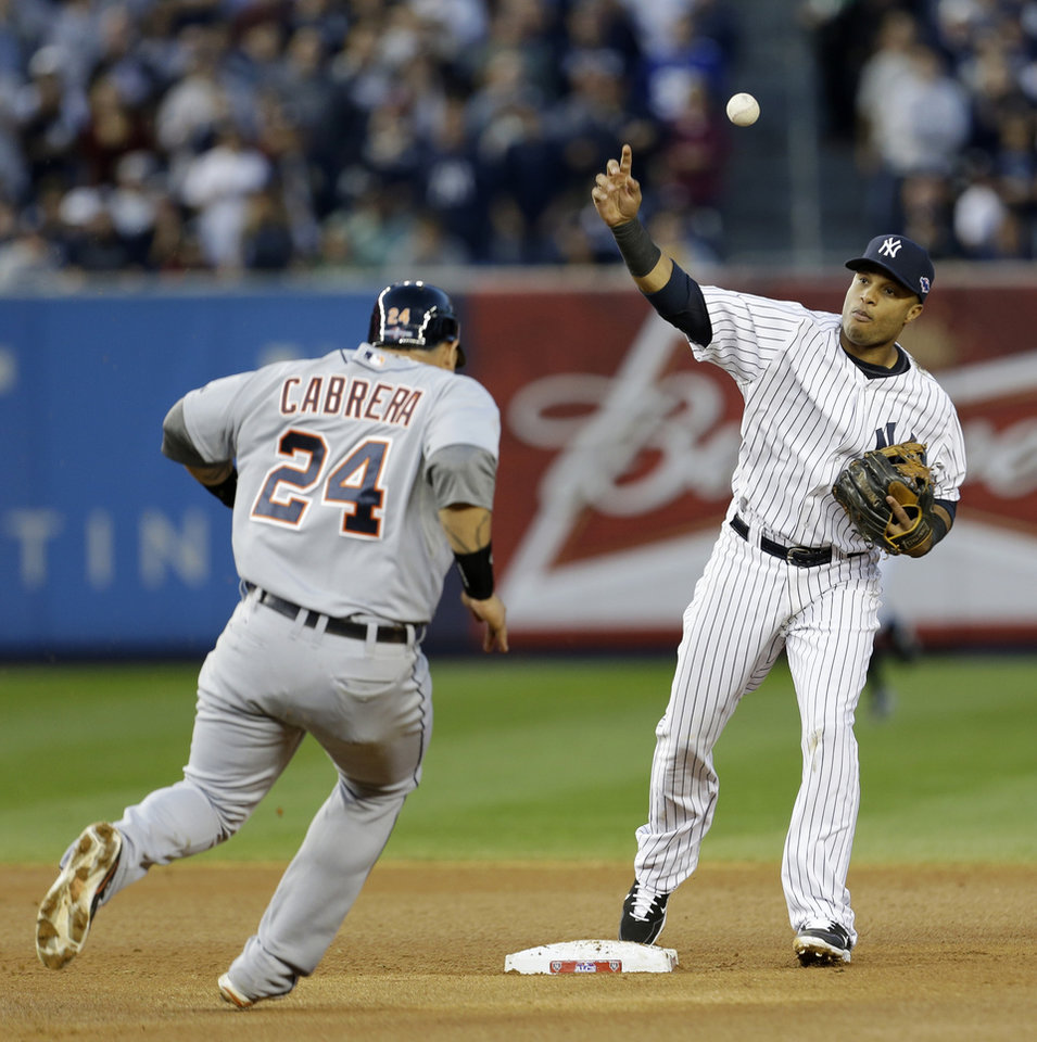 Photo -   New York Yankees' Robinson Cano looses control of the ball after forcing out Detroit Tigers' Miguel Cabrera at second base in the seventh inning of Game 2 of the American League championship series Sunday, Oct. 14, 2012, in New York. Quintin Berry scored on the play. (AP Photo/Paul Sancya )