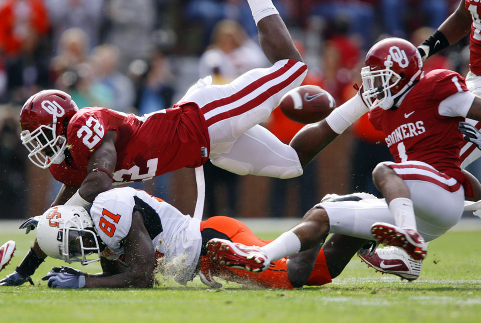 Photo - Oklahoma's Keenan Clayton (22) hits Oklahoma State's Justin Blackmon (81) forcing the ball loose during the first half of the Bedlam college football game between the University of Oklahoma Sooners (OU) and the Oklahoma State University Cowboys (OSU) at the Gaylord Family-Oklahoma Memorial Stadium on Saturday, Nov. 28, 2009, in Norman, Okla. The fumble was overturned on official review. 