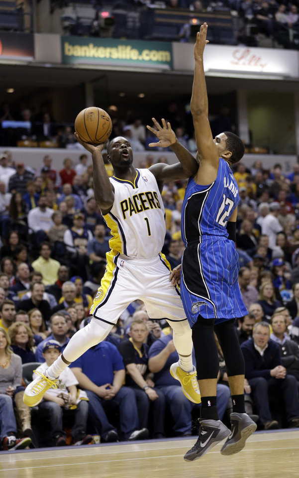 Photo - Indiana Pacers guard Lance Stephenson, left, holds off Orlando Magic forward Tobias Harris as he shoots in the second half of an NBA basketball game in Indianapolis, Monday, Feb. 3, 2014. The Pacers defeated the Magic 98-79. (AP Photo/Michael Conroy)