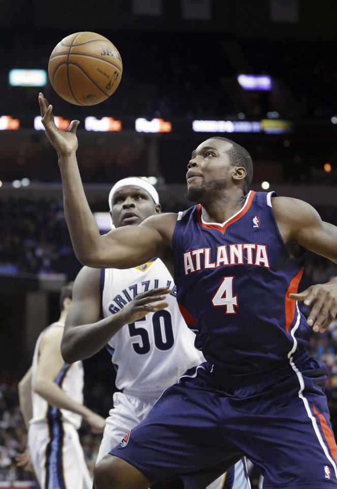 Photo - Atlanta Hawks' Paul Millsap (4) grabs a pass in front of Memphis Grizzlies' Zach Randolph (50) in the first half of an NBA basketball game in Memphis, Tenn., Sunday, Jan. 12, 2014. (AP Photo/Danny Johnston)