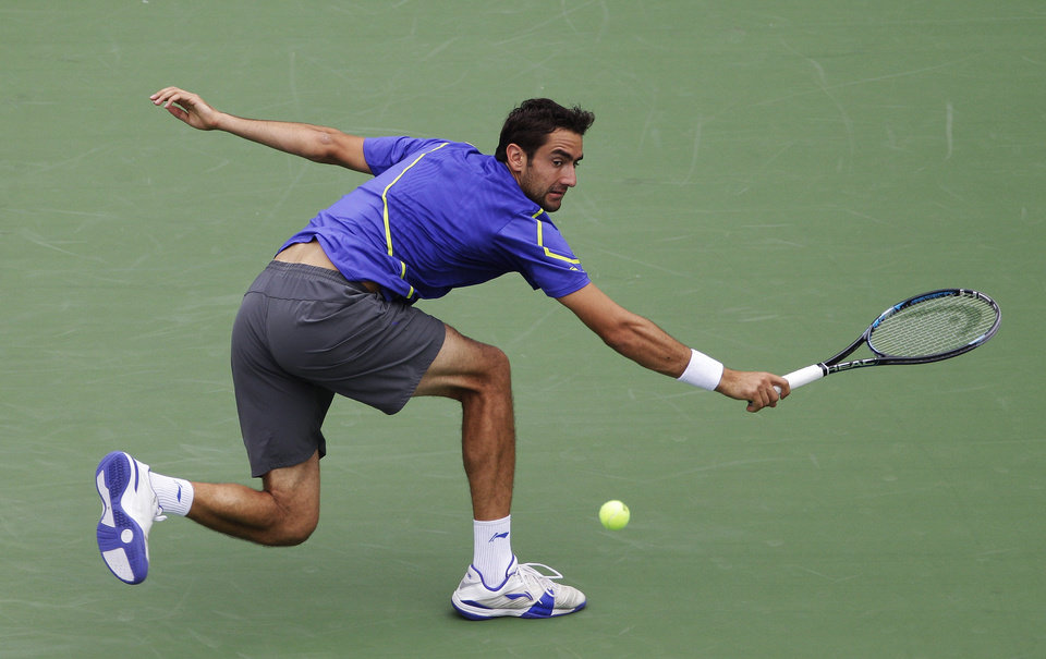 Photo -   Marin Cilic, of Croatia, returns a shot to Slovakia's Martin Klizan in the fourth round of play at the 2012 US Open tennis tournament, Monday, Sept. 3, 2012, in New York. (AP Photo/Kathy Willens)