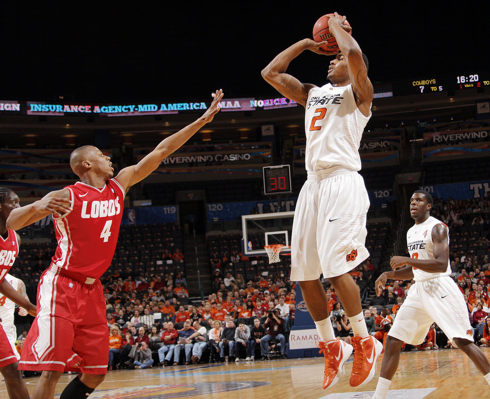 Photo - OSU's Le'Bryan Nash (2) shoots over Chad Adams (4) of UNM in front of OSU's Jean-Paul Olukemi (0) in the first half during the Bill Russell men's college basketball game of the Ramada All-College Classic between the Oklahoma State University Cowboys and the University of New Mexico Lobos at the Chesapeake Energy Arena in Oklahoma City, Saturday, Dec. 17, 2011. Photo by Nate Billings, The Oklahoman