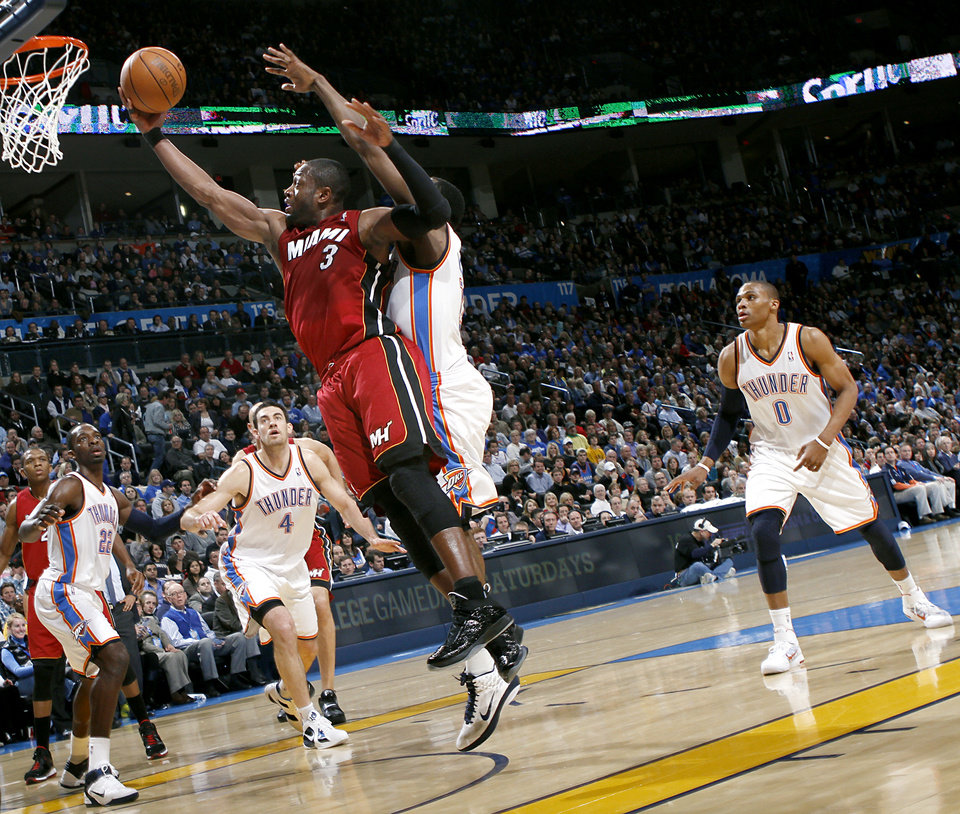 Photo - Miami's Dwyane Wade puts in a shot in front of Oklahoma City's James Harden and the Thunder defense during their NBA basketball game at the OKC Arena in Oklahoma City on Thursday, Jan. 30, 2011. Photo by John Clanton, The Oklahoman