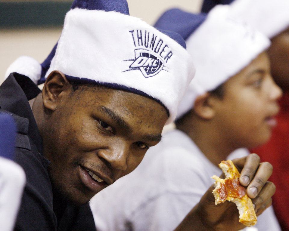 Photo - CHARITY / DONATE / DONATION / CHILD / KIDS: NBA basketball player Kevin Durant of the Oklahoma City Thunder eats pizza during a holiday party for children in the after school program at Pilot Recreation Center, 1435 NW 2nd Street, in Oklahoma City, Wednesday, Dec. 17, 2008. At the end of the party, Kevin Durant gave the children winter coats, hats and gloves donated by Nike. BY NATE BILLINGS ORG XMIT: KOD