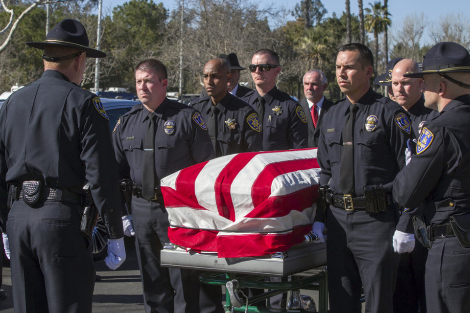 FILE - This Feb. 13, 2013 file photo shows Riverside Police officers carrying the casket of fellow Riverside Police officer Michael Crain, during the burial ceremony at the Riverside National Cemetery in Riverside, Calif.  Wednesday, Feb. 13, 2013. The 34-year-old Crain was ambushed in his patrol car on Feb. 7. Authorities believe the shooter was ex-Los Angeles policeman Christopher Dorner.  (AP Photo/Damian Dovarganes, File)
