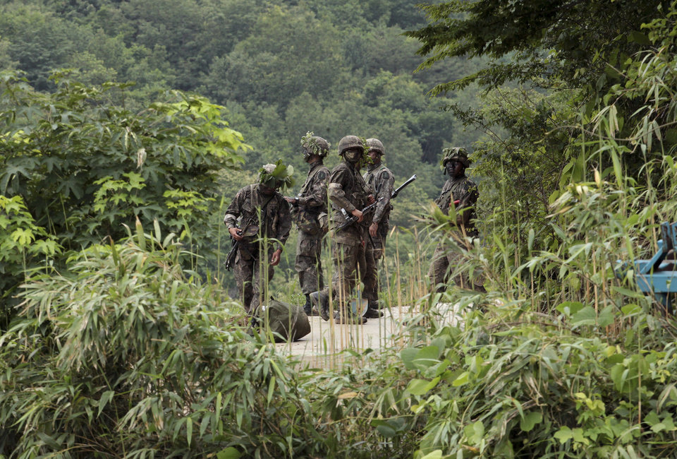 Photo - South Korean army soldiers search for a South Korean soldier who is on the run after a shooting incident in Goseong, South Korea, Sunday, June 22, 2014.  The military searched Sunday for an armed South Korean soldier who fled after killing five of his comrades and wounding seven at an outpost near the North Korean border.(AP Photo/Ahn Young-joon)