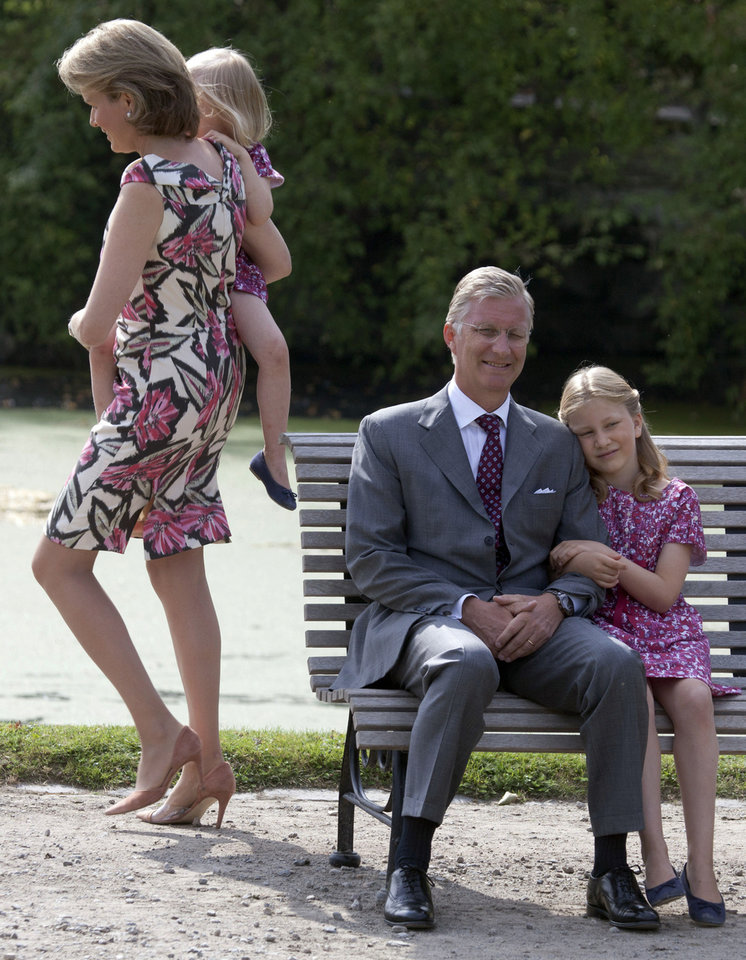 File - In this Sunday, Sept. 2, 2012 file photo Belgium's Crown Prince Philippe, second from right, sits with his daughter Princess Elisabeth as Princess Mathilde, left, walks with her daughter Princess Eleonore in the grounds of the Royal Palace in Laeken, Belgium. Albert II�s kingdom is increasingly threatened by royal-bashing separatists seeking the breakup of Belgium. Now, a book dipping deep into the privacy of kings and princes is adding insult to injury. With its back against the wall, the royal palace sought to strike back in the week of Oct. 29, 2012, seeking action against the journalist who published the book ��Royal Questions�� which is sometimes as rich on dangerous liaisons as it is on the use of anonymous sources. (AP Photo/Virginia Mayo, File)