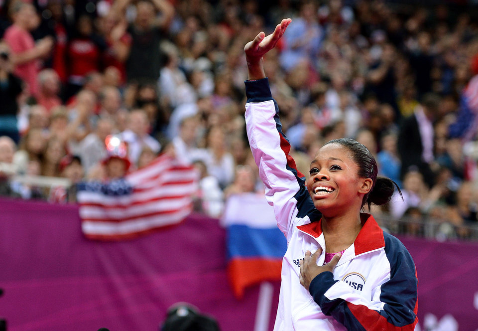 U.S. gymnast Gabby Douglas waves to the crowd after winning gold in the individual all-around in London on Thursday. Douglas is the fourth American gymnast to win the gold medal in the women�s all-around. Los Angeles Times/MCT photo