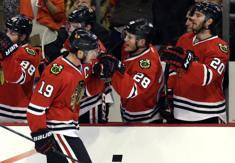 Photo - Chicago Blackhawks' Jonathan Toews (19) celebrates with teammates after scoring hi goal during the first period  in Game 2 of an NHL hockey second-round playoff series against the Minnesota Wild in Chicago, Sunday, May 4, 2014. (AP Photo/Nam Y. Huh)