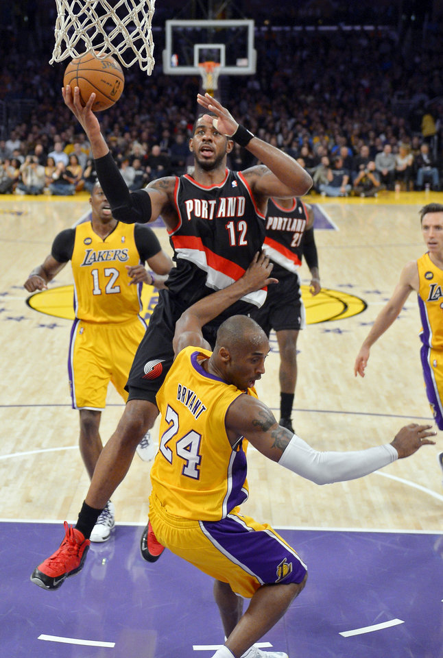 Photo - Portland Trail Blazers forward LaMarcus Aldridge, top, goes up for a shot as Los Angeles Lakers guard Kobe Bryant falls during the first half of their NBA basketball game, Friday, Feb. 22, 2013, in Los Angeles. (AP Photo/Mark J. Terrill)