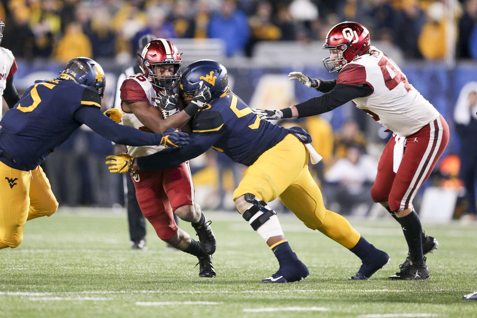 Photo - West Virginia Mountaineers defensive lineman Ezekiel Rose (5) and West Virginia Mountaineers defensive lineman Dante Stills (55) tackle Oklahoma Sooners running back Kennedy Brooks (26) during the NCAA football game between the Oklahoma Sooners and the West Virginia Mountaineers at Mountaineer Field at Milan Puskar Stadium in Morgantown, W.Va on Friday, November 23, 2018. IAN MAULE/Tulsa World