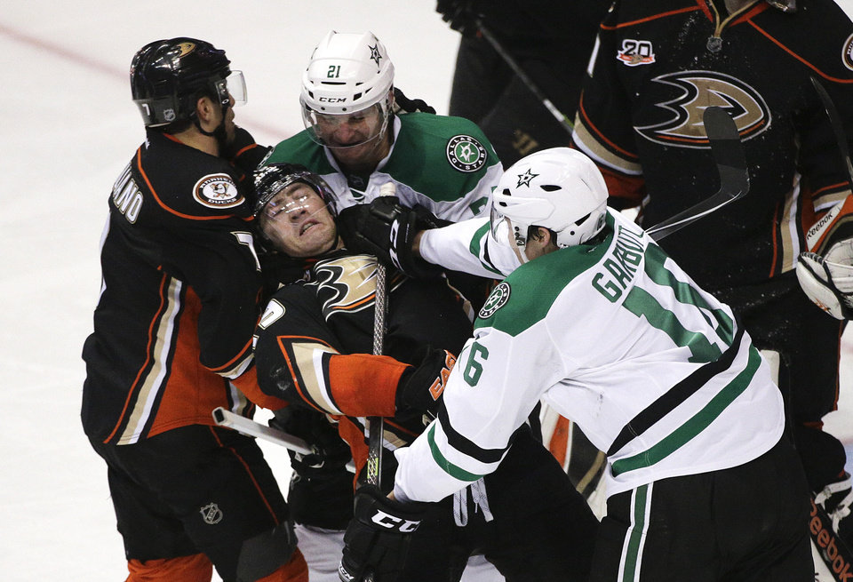 Photo - Anaheim Ducks' Stephane Robidas, center, is shoved by Dallas Stars' Ryan Garbutt, right, during the second period in Game 1 of the first-round NHL hockey Stanley Cup playoff series on Wednesday, April 16, 2014, in Anaheim, Calif. (AP Photo/Jae C. Hong)