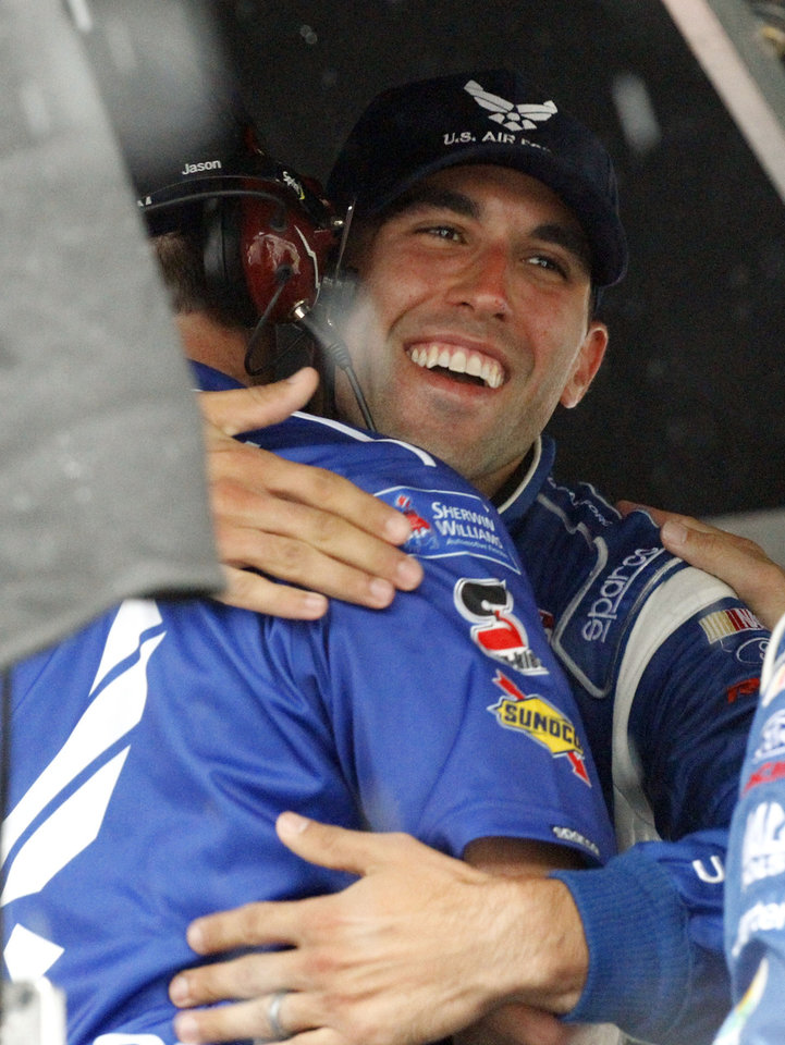 Photo - Aric Almirola celebrates with a crew member in his pit stall after it was announced he won the rain shortened NASCAR Sprint cup Series auto race at Daytona International Speedway in Daytona Beach, Fla., Sunday, July 6, 2014. (AP Photo/Terry Renna)