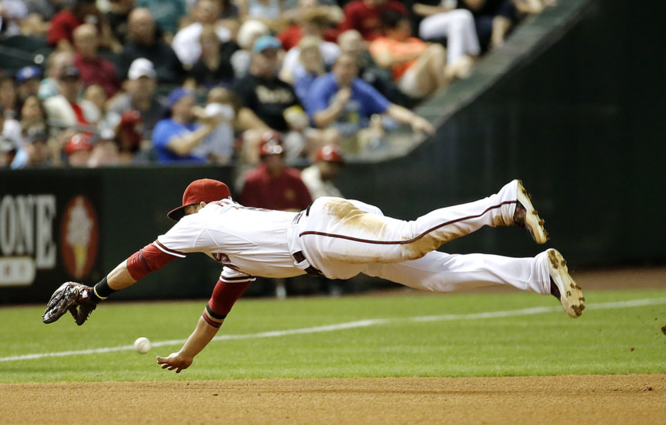 Photo - Arizona Diamondbacks' Martin Prado can't stop a ball that went for a base hit by Los Angeles Dodgers' Dee Gordan during the fourth inning of a baseball game on Friday, May 16, 2014, in Phoenix. (AP Photo/Matt York)