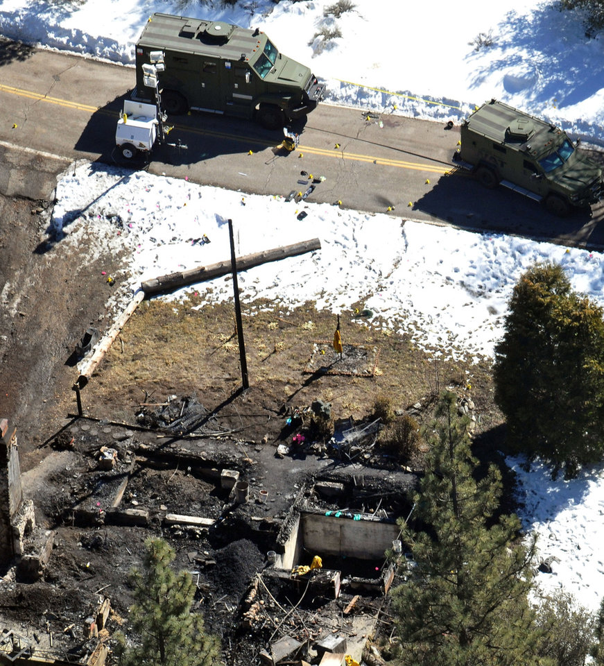 In this aerial photo, law enforcement authorities investigate the burnt-out cabin Wednesday, Feb. 13, 2013, where quadruple-murder suspect Christopher Dorner is believed to have died after barricading himself inside during a Tuesday stand-off with police in the Angeles Oaks area of Big Bear, Calif. San Bernardino Sheriff\'s Deputy Jeremiah MacKay was killed and another wounded during the shootout with Dorner. (AP Photo/The Sun, John Valenzuela)