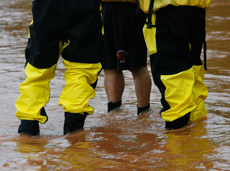 Photo - Water rescue crews with the Oklahoma City Fire Department stand in flood water during a rescue effort. Torrential rain caused flooding in Oklahoma City, Monday, June 14, 2010.     by Jim Beckel, The Oklahoman