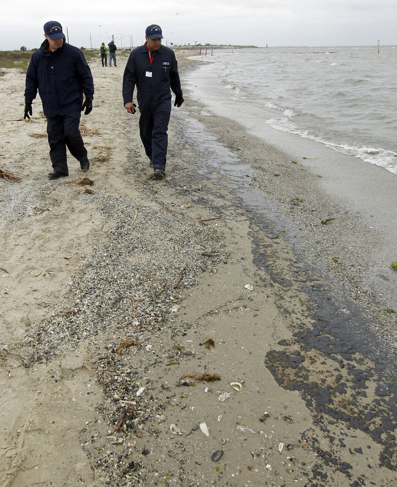Photo - United States Coast Guardsmen inspect  oil washing ashore along Boddeker Road in Galveston, Texas on Sunday March 23, 2014. More than 160,000 gallons of heavy fuel oil is leaking from a disabled barge, that collided with a ship Saturday near the Texas City Dike. (AP Photo/The Daily News, Jennifer Reynolds)