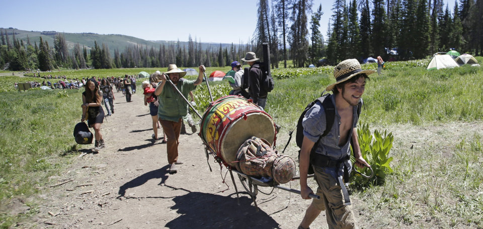 Photo - People walk along a trail in the Rainbow Family encampment Tuesday, July 1, 2014, in the Uinta National Forest, Utah. About 4,000 members of a counterculture group known as the Rainbow Family have poured into the woods about 60 miles east of Salt Lake City for an annual festival that culminates in a four-day celebration beginning Tuesday. (AP Photo/Rick Bowmer)