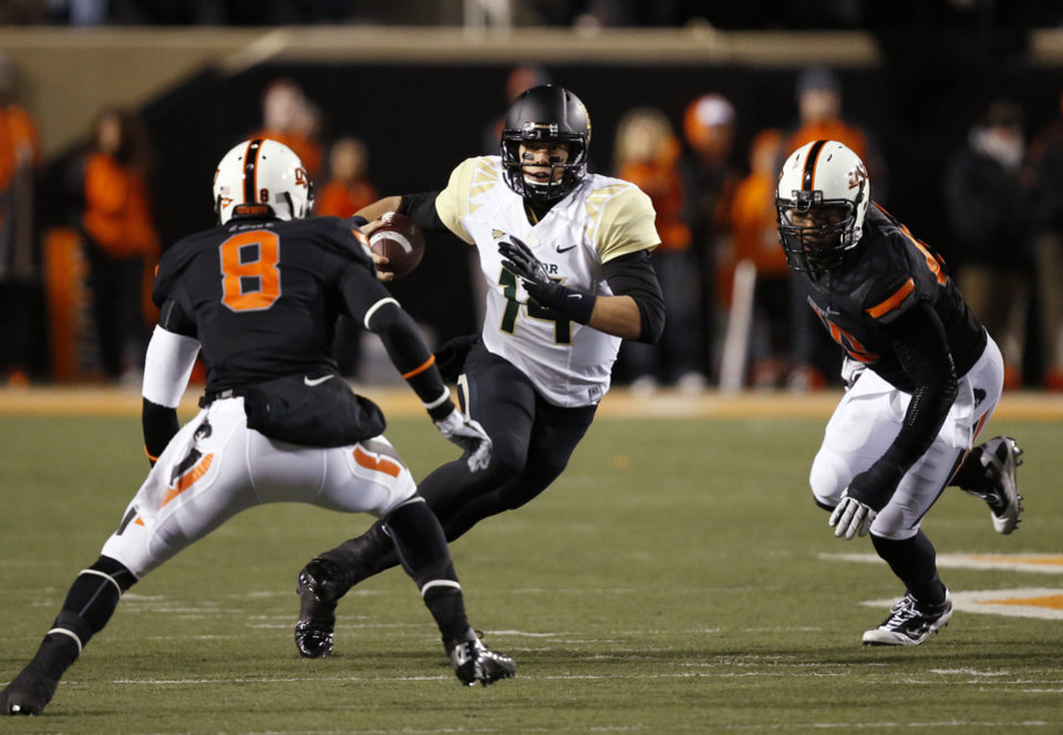 Photo - Baylor quarterback Bryce Petty (14) carries past Oklahoma State safety Daytawion Lowe (8) and defensive end Tyler Johnson (40) in the first quarter of an NCAA college football game in Stillwater, Okla., Saturday, Nov. 23, 2013. (AP Photo/Sue Ogrocki)