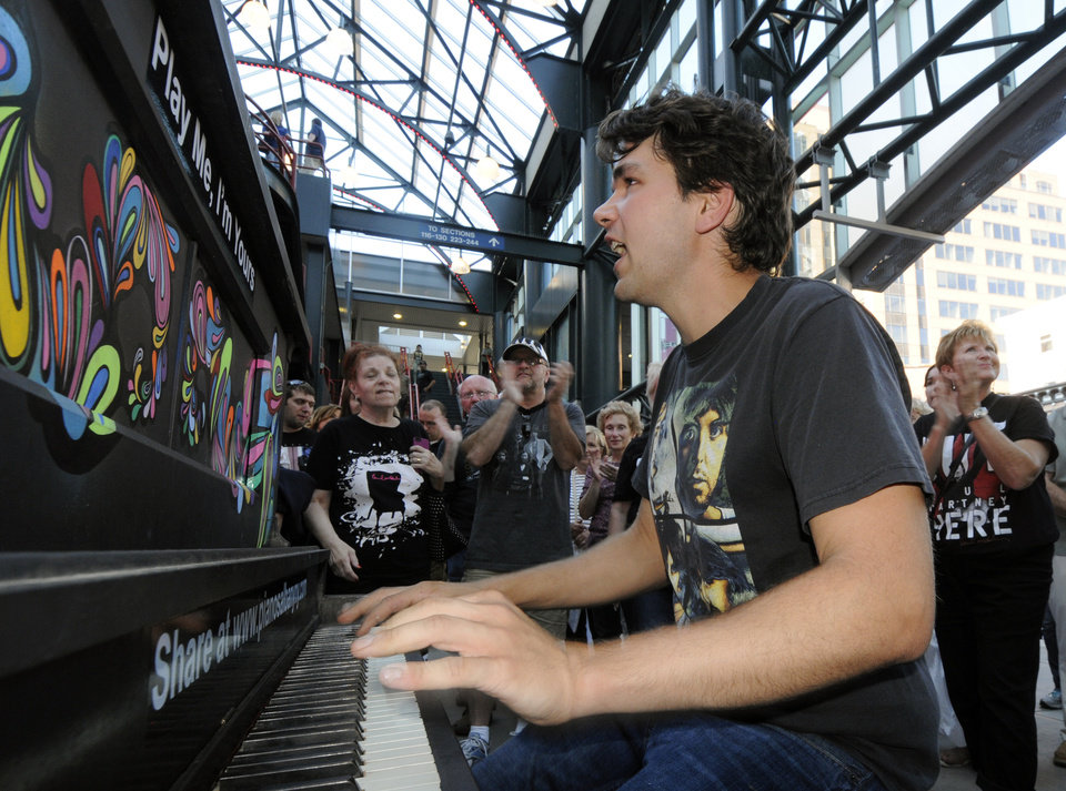 "Photo - Brian Tiernan of Rensselaer, N.Y., plays a piano and sings Beatles songs with fans before the Paul McCartney ""Out There"