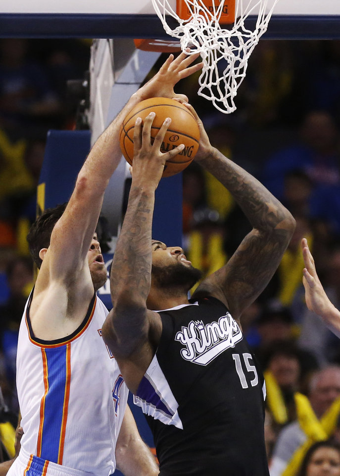 Photo - Sacramento Kings center DeMarcus Cousins (15) shoots in front of Oklahoma City Thunder forward Nick Collison (4) in the fourth quarter of an NBA basketball game in Oklahoma City, Sunday, Jan. 19, 2014. Oklahoma City won 108-93. (AP Photo/Sue Ogrocki)