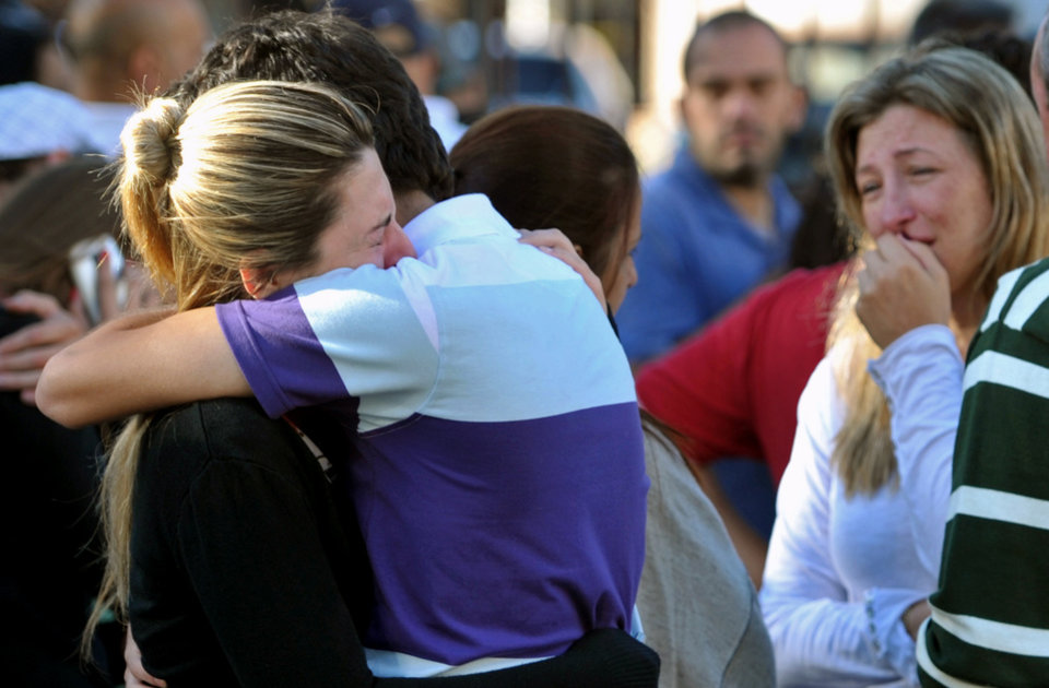 Photo - Relatives of victims react near the Kiss nightclub in Santa Maria city,  Rio Grande do Sul state, Brazil, Sunday, Jan. 27, 2013.  According to police more than 200 died in the devastating nightclub fire in southern Brazil.  Officials say the fire broke out at the club while a band was performing. (AP Photo/Ronald Mendes-Agencia RBS)